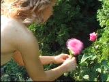 מאוננת עם פרח שווה על מיטת שיזוף
